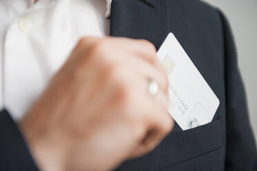 Businessman removing credit card from suit pocket - DIGF12669