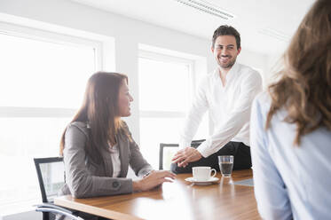 Happy business colleagues discussing in brightly lit board room - DIGF12687