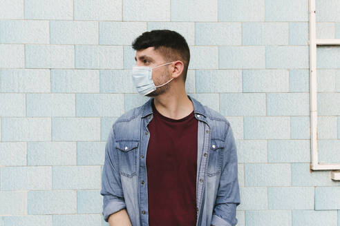 Man with protective mask in front of blue tiled wall - AGGF00067