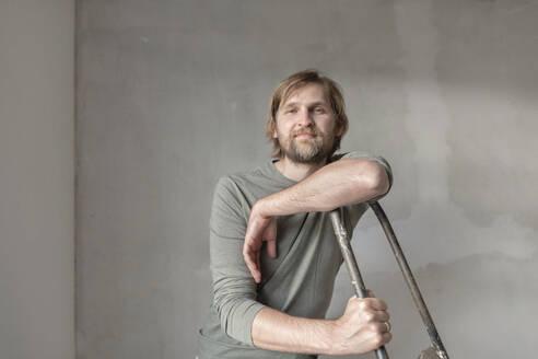 Confident man leaning on ladder during renovation - EYAF01090
