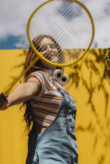 Young woman looking through badminton racket over yellow wall during sunny day - AFVF06444