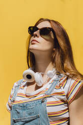 Beautiful young woman wearing sunglasses and headphones against yellow wall during sunny day - AFVF06453
