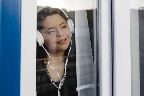 Thoughtful woman with down syndrome listening music while looking through window at home - DCRF00234