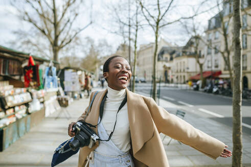 Cheerful woman holding DSLR camera on sidewalk in Paris, France - KIJF03064