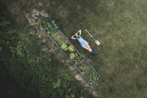 Drone shot of woman with hands behind head lying by raised bed on land - HMEF00956