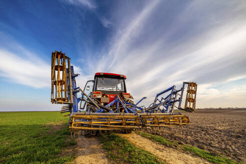 Tractor on agricultural field against sky - NOF00099