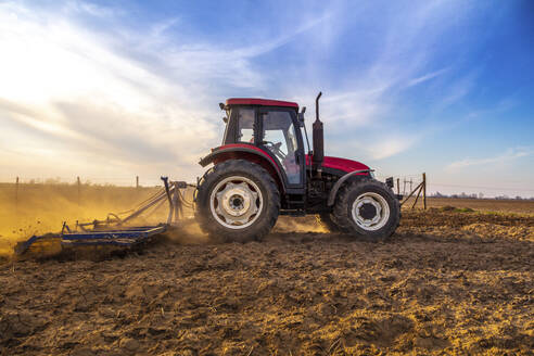 Man in tractor plowing agricultural field against cloudy sky - NOF00102