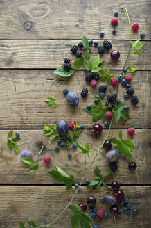 Fresh berries, plums and cherries on wooden surface - ASF06624