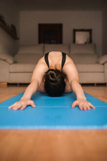 Woman exercising on mat in living room at home - GRCF00262