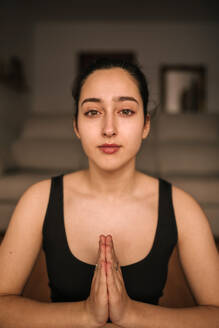 Close-up of confident woman meditating in prayer position at home - GRCF00265