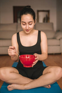 Young woman holding breakfast bowl while sitting on exercise mat at home - GRCF00268