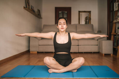 Young woman with arms outstretched exercising while sitting on mat at home - GRCF00271