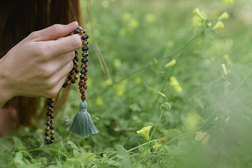 Close-up of mid adult woman holding prayer beads meditating over grassy land - LVVF00002