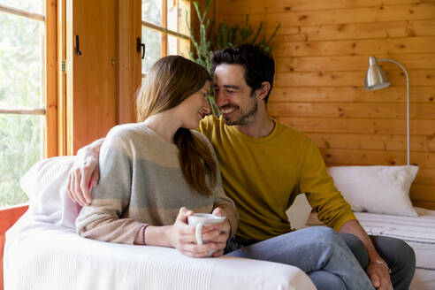 Smiling couple romancing while sitting on sofa in log cabin - LVVF00005