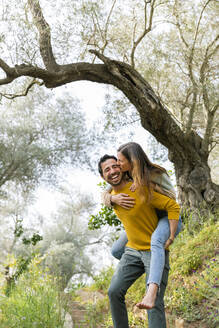 Cheerful man piggybacking romantic girlfriend while standing against trees at countryside - LVVF00023