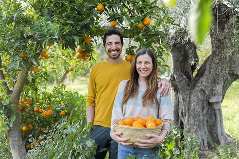 Smiling couple with oranges standing against trees in organic farm - LVVF00035