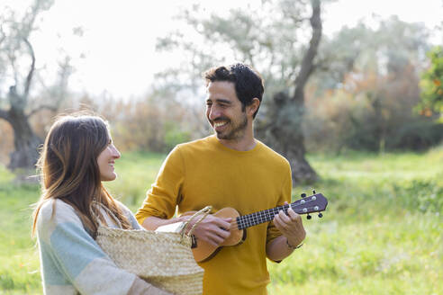 Woman carrying wicker basket while happy man playing guitar at countryside - LVVF00041