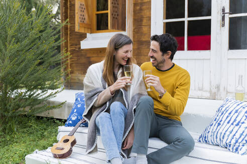 Laughing couple holding wineglasses while sitting against log cabin - LVVF00053