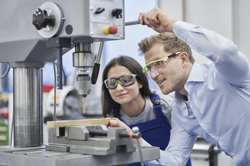 Male manager drilling metal while training female worker in metal industry - RORF02215