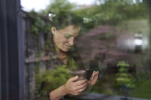 Smiling mid adult woman using smart phone at home seen through window - AUF00553