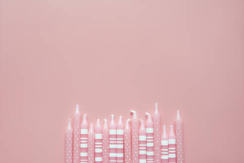 Studio shot of row of pink colored birthday candles - SKCF00606