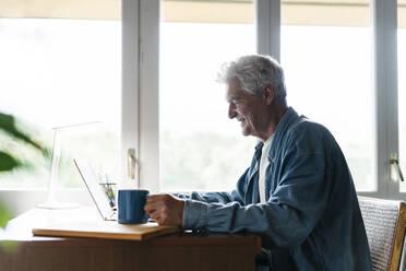 Happy senior man holding coffee mug while using laptop at home - AFVF06539