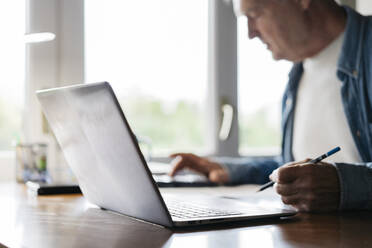 Senior man using calculator and laptop while writing at home - AFVF06542