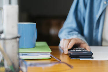 Senior man holding calculator while working at table - AFVF06545