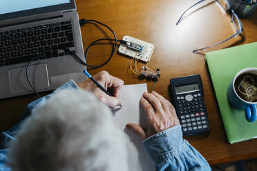 Cropped image of senior man making diagram on paper while repairing laptop at home - AFVF06548