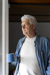 Thoughtful senior man holding coffee mug while looking through window at home - AFVF06551