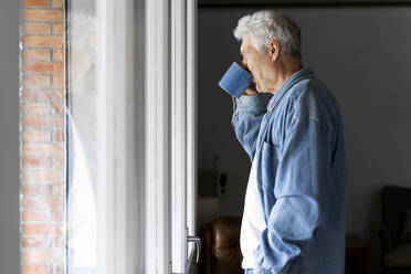 Thoughtful senior man drinking coffee while standing by window at home - AFVF06554