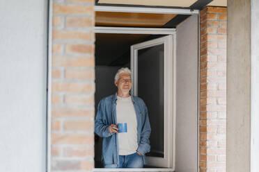 Thoughtful senior man holding coffee mug while looking through window - AFVF06557