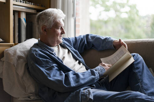 Senior man reading book while relaxing on sofa at home - AFVF06560