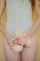 Young woman with pink flower wearing pastel blue swiming suit - AFVF06569