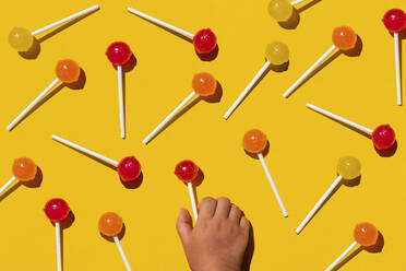 Colorful lollipop sweet candies pattern on yellow background with child hand picking a sweet - GEMF03814