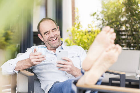 Cheerful mature man using smart phone while sitting with coffee cup at back yard - UUF20455