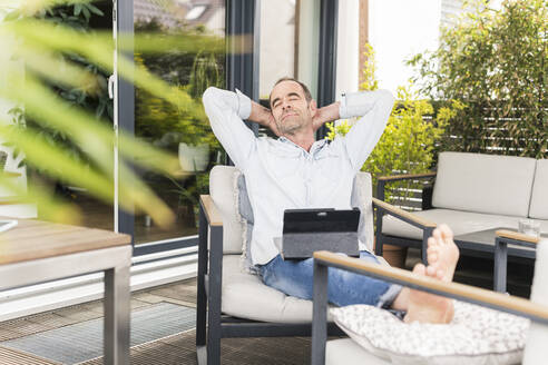 Relaxed businessman with hands behind head sitting on chair at back yard - UUF20458