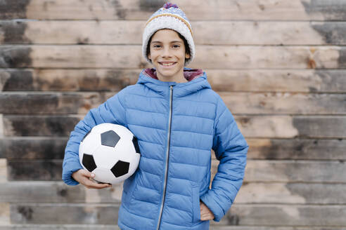 Smiling boy wearing warm clothing holding soccer ball while standing against wall - JCZF00120