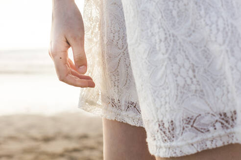 Close-up of young woman wearing white dress standing at beach - FVSF00386