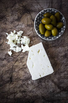 Feta cheese and bowl of fresh olives on wooden surface - GIOF08352