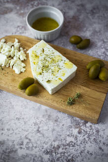 Cutting board with feta cheese and olives - GIOF08358