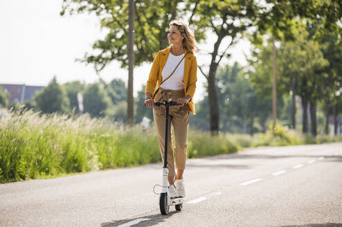Mature woman riding electric push scooter on road during sunny day - UUF20530