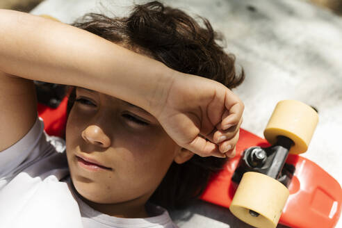 Close-up of thoughtful boy looking away while lying on skateboard - VABF02978