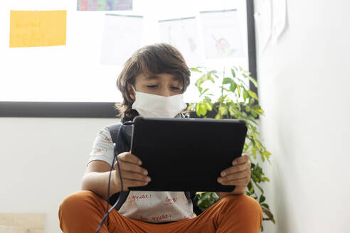 Boy wearing face mask using digital tablet while sitting in school - VABF02981