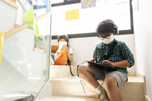 Boys wearing masks studying while sitting at distance on steps in school - VABF02993