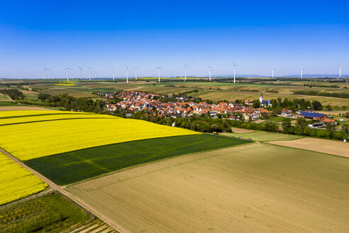 Germany, Rhineland-Palatinate, Gabsheim, Helicopter view of countryside fields and village in summer with wind farm in background - AMF08175