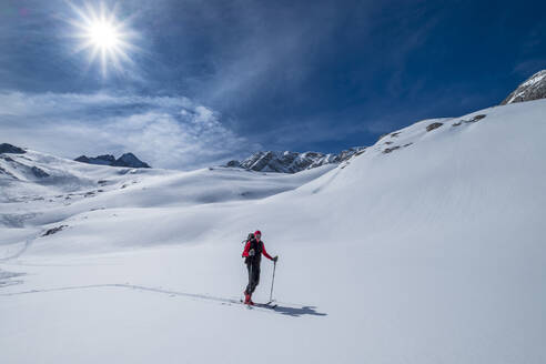 Senior man skiing on snow covered land against sky during sunny day, Dachstein, Austria - HAMF00627