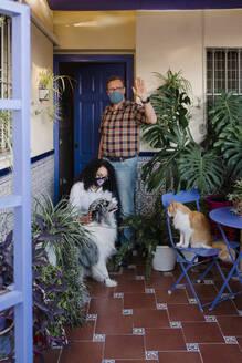 Man wearing mask waving hand while woman petting dog in yard - AGGF00077