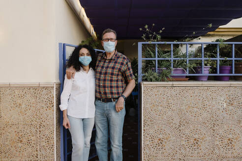 Couple wearing masks standing at gate of house - AGGF00080