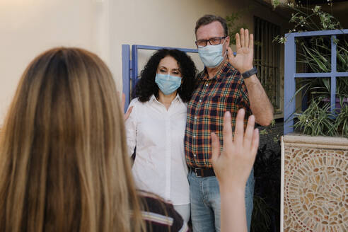 Couple wearing masks waving hands to neighbor while standing at gate of house - AGGF00083